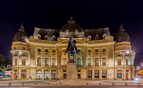 Frontal view of the Central University Library of Bucharest and Carol I statue, central Bucharest, Romania.