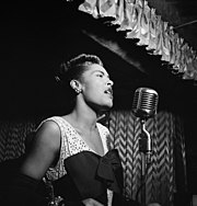 A black and white close-up picture of Billie Holiday singing into a microphone.