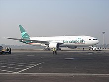 A white aircraft with Bangladesh written in green on the front half below the windows with a dark green colour on the tail facing right