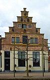foto van Huis met onder gepleisterde trapgevel met lelie-ankers, zandstenen waterlijsten en afdekplaten (Anne Hubertshuis)