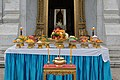 Buddhist offering table with fruits meat rice confectionery flowers and candles at Bangkok City Pillar Shrine Thailand.jpg