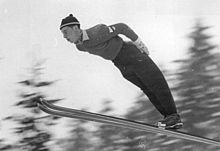 A man, in ski suit, is in flight of a ski jump, he is leaning forwards, in the middle of his jump.