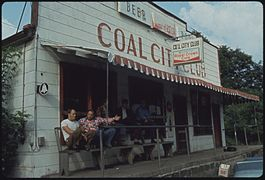 "A white building with 'COAL CITY CLUB' in painted in maroon. Some miners sit on benches outside; others ""hunker down""."