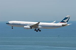 A white A330 over water, marked with Cathay Pacific and its logo on the vertical stabiliser, gear extended