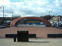 A brick-red, elliptically curved arch, twice as wide as it is high, over an open area with a brick-red surface