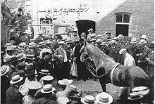 Photo en noir et blanc présentant une cour où des hommes et des femmes en chapeaux entourent un cheval.