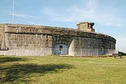 View of the front exterior of the fort showing an arc of casemates, with a structure on the roof
