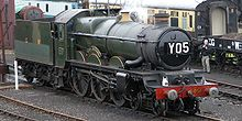 A green steam engine with three pairs of large wheels and two smaller ones and the reporting letters Y05 on the front