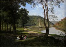 Four people sit together on a shaded lawn beside a riverside path. A small boat sails on the river, which bends away into a gap between sunlit wooded hills.