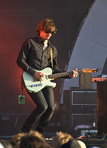 Middleton is playing his guitar with his left hand on the fret board and right hand on the strings. His knees are flexed, he wears dark glasses, dark pants and a dark shirt. His stage pass dangles from the end of the guitar. His hair is brown and hangs partly into his eyes. He wears a wide ring on his right hand's fourth finger. There is band equipment nearby.