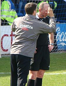 Referee Mike Dean receiving treatment after being struck by a projectile in a South Wales derby in 2009 Dean, Mike (2).jpg
