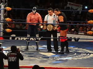 El Texano Jr. and Blue Demon Jr. holding the AAA Mega Championship belt in a wrestling ring