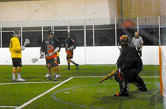 Box Lacrosse League - Grand Rapids Dragonfish shooter (black and orange) and Detroit Coney Dogs defender (yellow) look on as Coney Dogs goalie Devan Mighton (black) traps ball (2012).