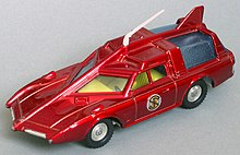 The photograph depicts a scale toy replica of a futuristic car that is deep red in colour and incorporates an angular bonnet and roof.