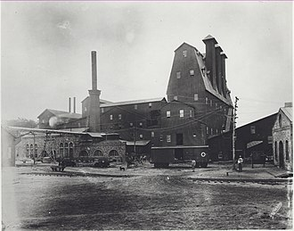 Edison Ore-Milling Company - The tower containing the magnetic ore separators at Ogden mine. The stone building is a power house or boiler house. c. 1895.