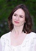 Foto de Emily Mortimer vestida de branco sobre um fundo verde