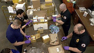 Controlled Substances Act - Drug enforcement administration agents inspect packages for illegal drug shipments at an international mail facility in New York