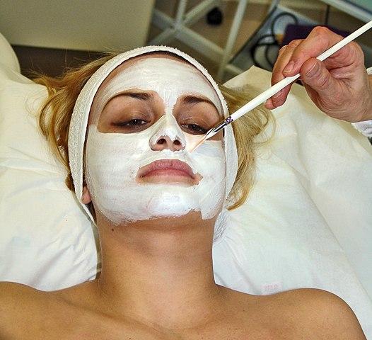 Eine Maske wird auf das Gesicht einer Frau angebracht.