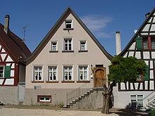 Maison à étage, au toit pointu, rosée, vue de face, dans un groupe de trois maisons similaires