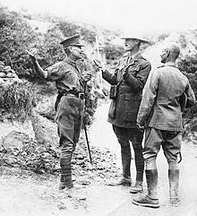 three men dressed in uniform standing on scrubby terrain, in conversation