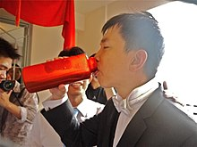 A groom drinking from a translucent red water bottle.