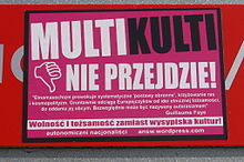 "A pink poster in Polish with headline MULTIKULTI / (thumb down) NIE PRZEJDZIE! (""multiculti will not pass!"")"