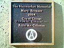 The plaque on Mary Brogger's Haymarket memorial as it has been vandalized with Anarchist symbols.