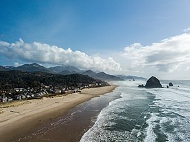 An aerial view of Cannon Beach with Haystack Rock in the background.