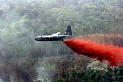 A MAFFS-equipped Air National Guard C-130 Hercules drops fire retardant on wildfires in Southern California