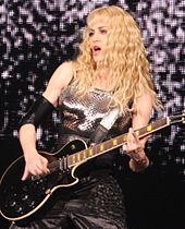 Madonna in a silver dress, playing electric guitar