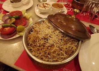 Hyderabadi cuisine - Hyderabadi Biryani with salad (left), Mirchi-ka-Salan (top right), and Dahi-ki-Chutney (top left). The layer of meat is hidden under the layer of rice.