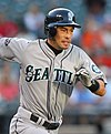 "A man in a gray baseball uniform running to the right. The uniform reads ""Seattle"" across the front, and has a sleeve patch with a teal and silver compass surrounded by ""Seattle Mariners"". The man is wearing a dark batting helmet."