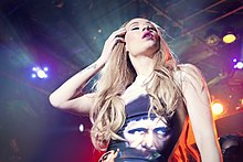 Iggy Azalea wearing a bodysuit with an image of a man on it