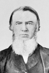 Black and white photograph of John Baker White, who has a beard and is wearing a suit.