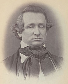 A round-faced man with wispy, dark hair wearing a dark jacket, white shirt, and dark tie with a large knot at the neck