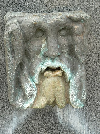Jublains - Detail of the fountain, located to the side of the church, with the representation of the god Oceanus, the symbol of Jublains
