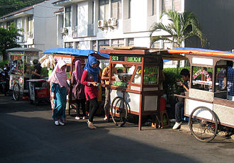 Food cart - Wooden traditional food carts lining Jakarta street, selling various Indonesian street foods.