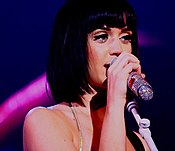Katy Perry with short, black hair singing into a silver sparkly microphone.