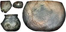 Photographie en couleurs sur fond noir de poteries à panse large et de tessons de poteries portant des incises obliques en forme de ruban.