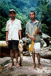Two Malagasy hunters stand near a stream, one holding a gun, the other holding a lemur with a white head.