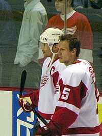 Photo de profil de Lidstrom portant le numéro 5 des Red Wings devant Yzerman portant le C de capitaine.
