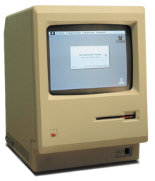 A beige, boxy computer with a small black and white screen showing a window and desktop with icons.