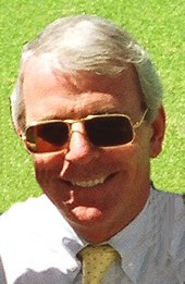 a smiling middle-aged man with grey hair, wearing sunglasses