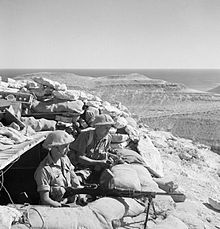 Two soldiers, with a machine gun and standing behind sandbags, look to the right out over a desert view.