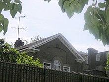 Photo sombre montrant la partie supérieure d'une maison (fenêtre arrondie, murs en briques et toit pointu), aperçue au-dessus d'un mur.