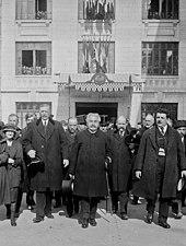 Zwart-witfoto van een groep individuen die met hun rug naar een officieel gebouw lopen;  in het midden een man met grijswit haar en een grijze snor met een hoed in zijn rechterhand en een wandelstok onder zijn linkerarm