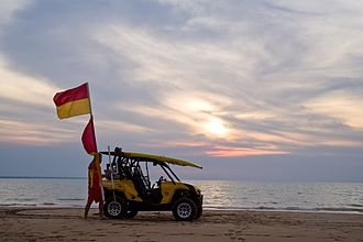 Surf lifesaving - Surf lifesaver taking in the flags at sunset Mindil Beach