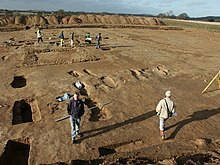 A photograph of a wide flat area of dirt, with a handful of men scattered across it engaged in some sort of work. In the near ground one man is standing looking at the camera. All the men cast long shadows across the picture.