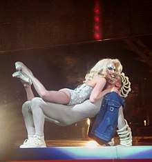 A man faces upwards with his feet on the ground and his knees bent at around 90 degrees, his arms supporting his upper body. A blond woman, wearing a shiny leotard lies on top of him. She has her lower legs kicked up in the air. She looks out with an expression of enjoying the situation. A spotlight highlights the man and woman in the foreground. The background is dimly lit with red lights.