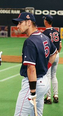 "A man in white pants, a dark blue baseball cap, and a dark blue baseball jersey with ""5"" on the back leans on a baseball bat in his left hand."